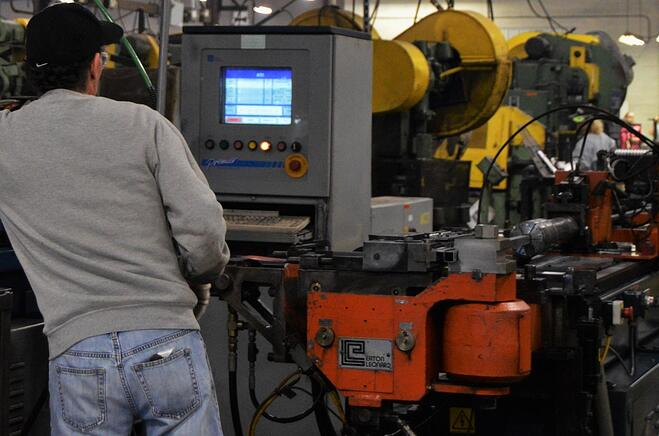 An engineer operating a steel tube fabrication machine