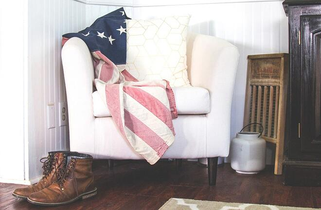 A pair of workboots in front of a chair with a patriotic blanket
