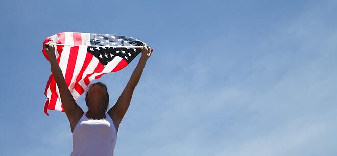 A woman holding an American flag above her head